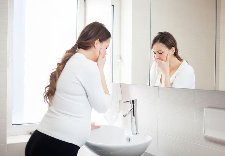 Woman covering her mouth by a sink.